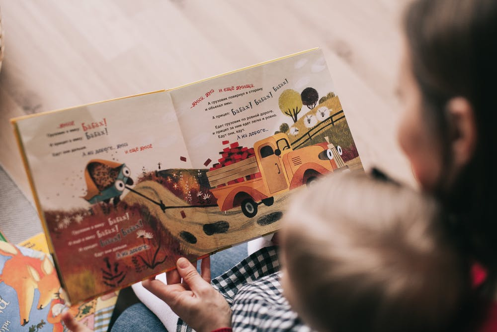 woman reading to a little child inside a childcare center